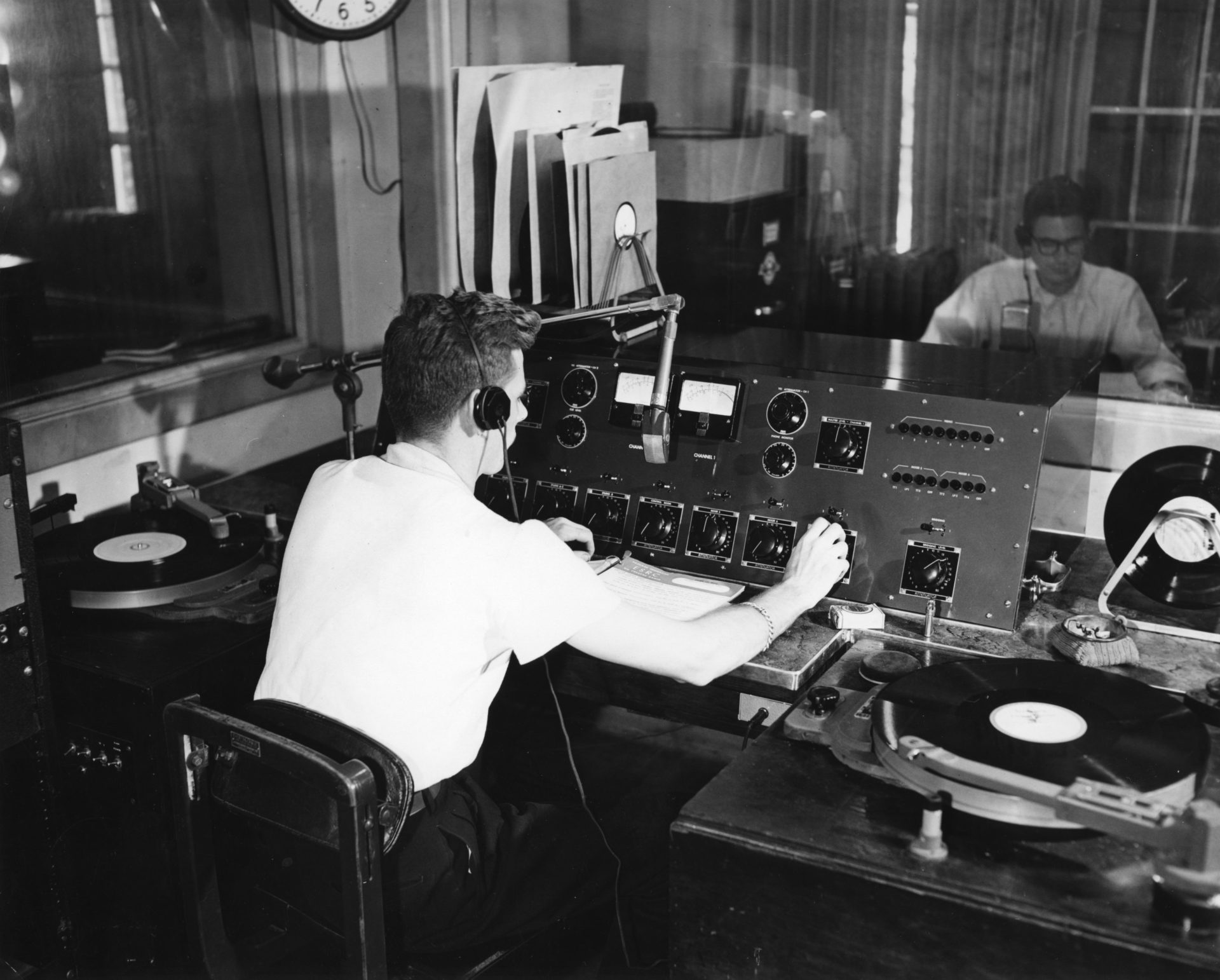 black and white photograph of a radio DJ in a studio in 1952