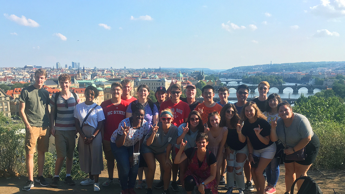 A group of students in the Global Leadership minor program stand together on top of a hill overlooking Prague