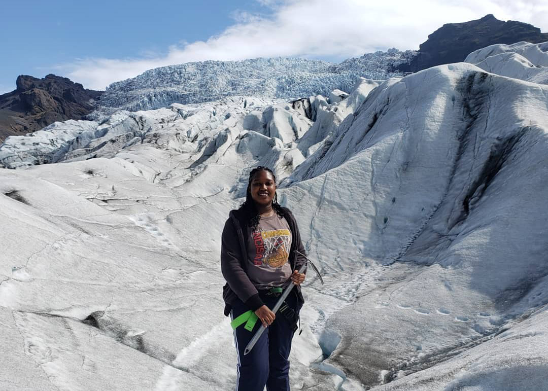 Safari Richardson stands in front of a glacier