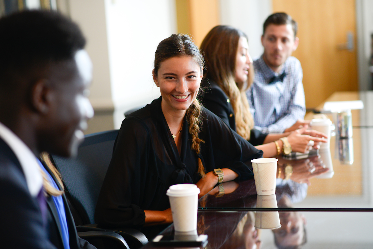 Woman sits at table smiling in conversation