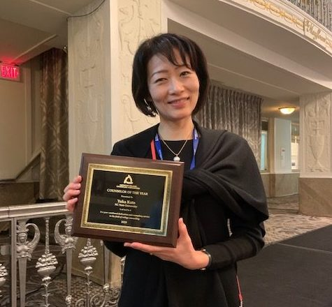 Yuka Kato holds her Counselor of the Year award from the American College Counseling Association