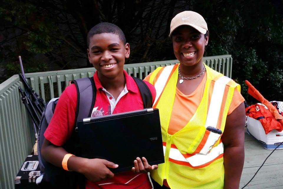 Angela Caraway presents a laptop to a student as part of the Caraway Foundation's 2014 Back to School Bash