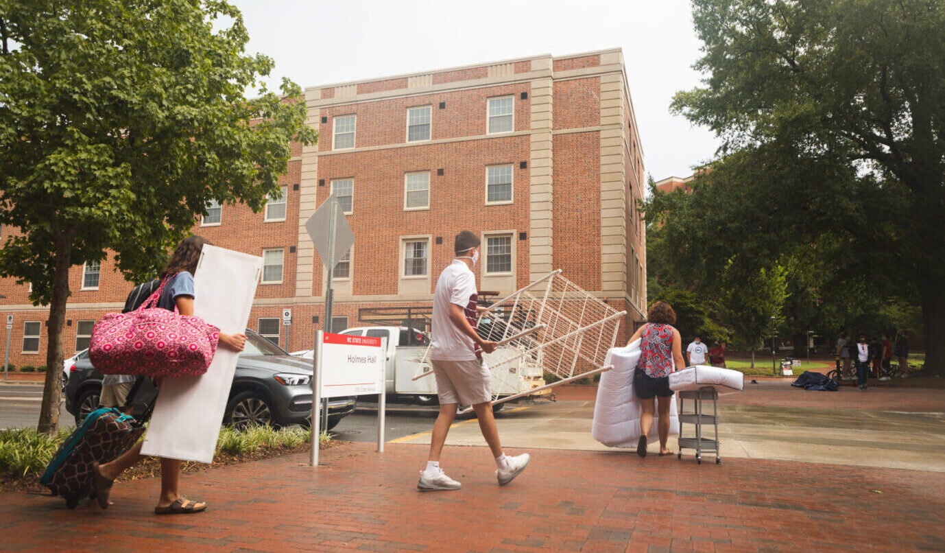 A new student and family carry their belongings towards a residence hall