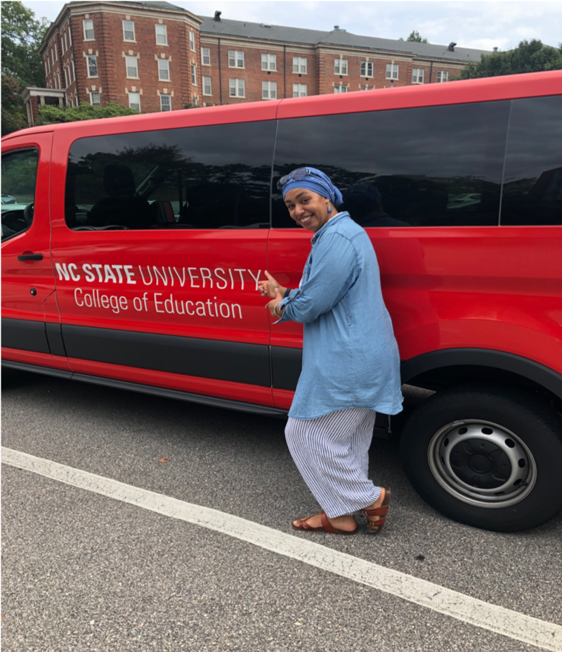 Hakima Harris poses next to a van for the College of Education