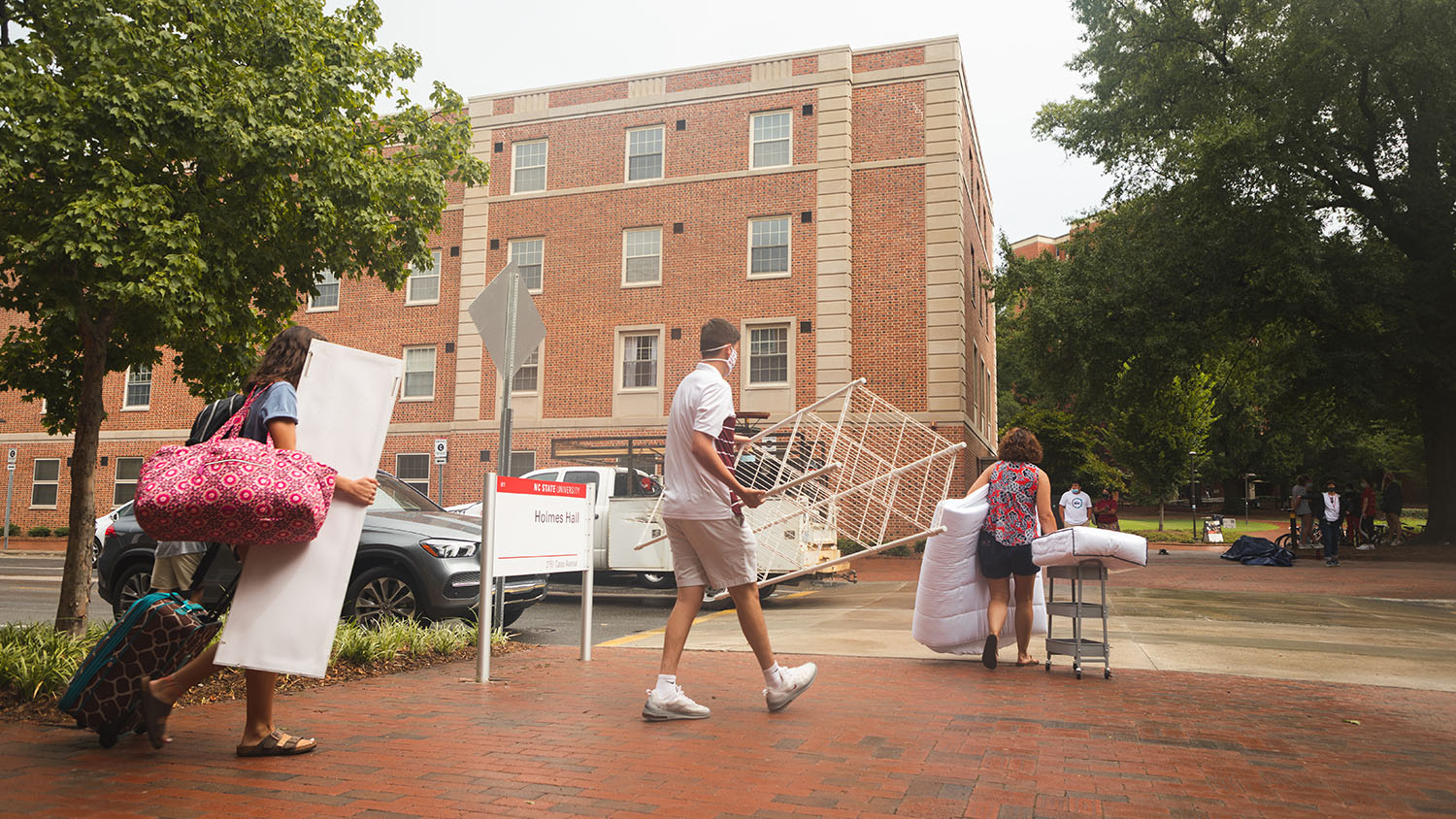 A new student carries luggage towards his residence hall