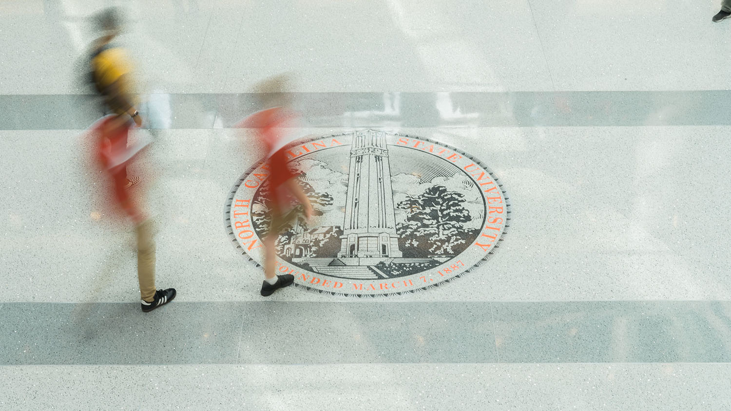 Students walk by the NC State seal in Talley Student Union