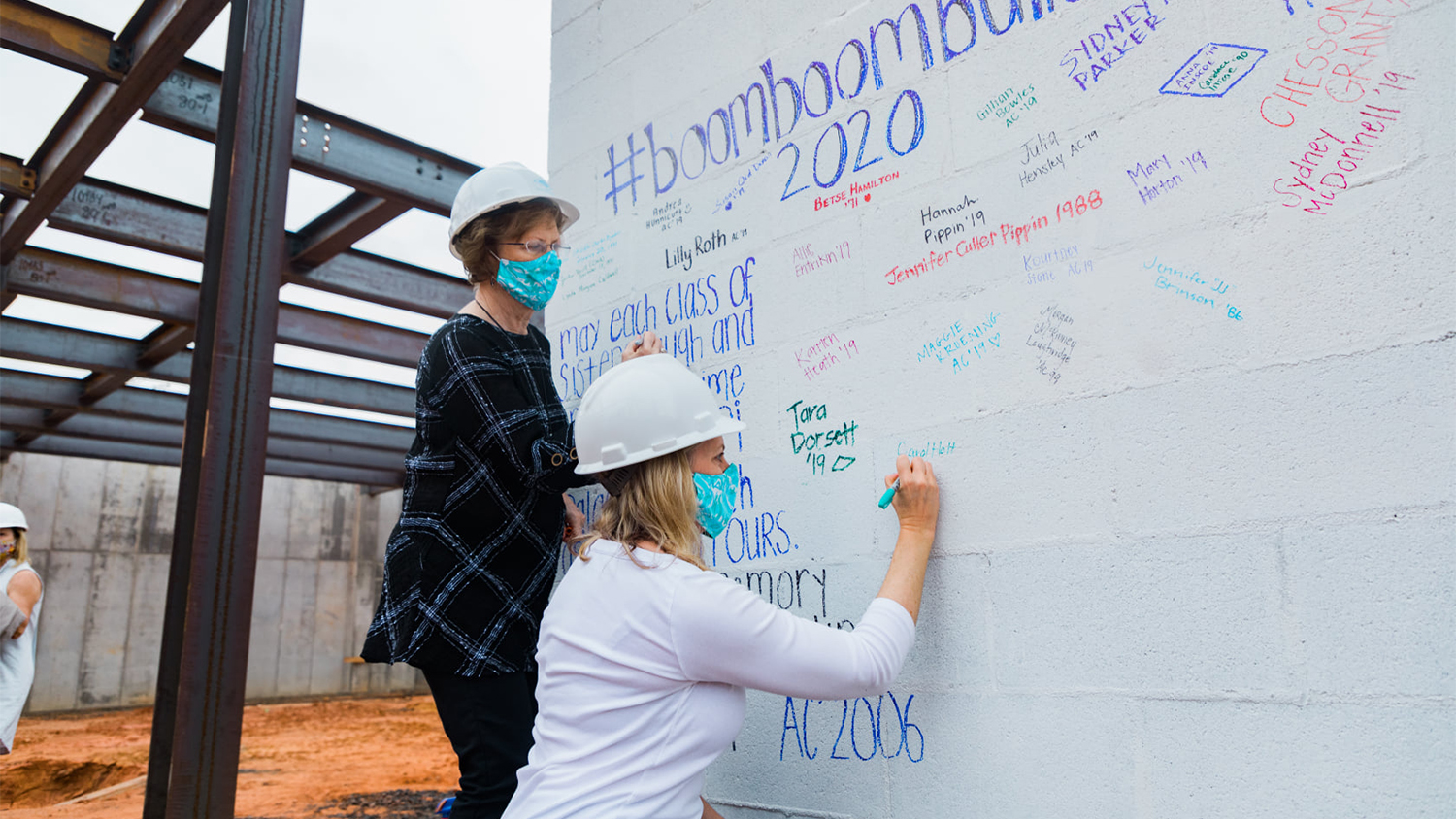 Members of Alpha Delta Pi sign the beam