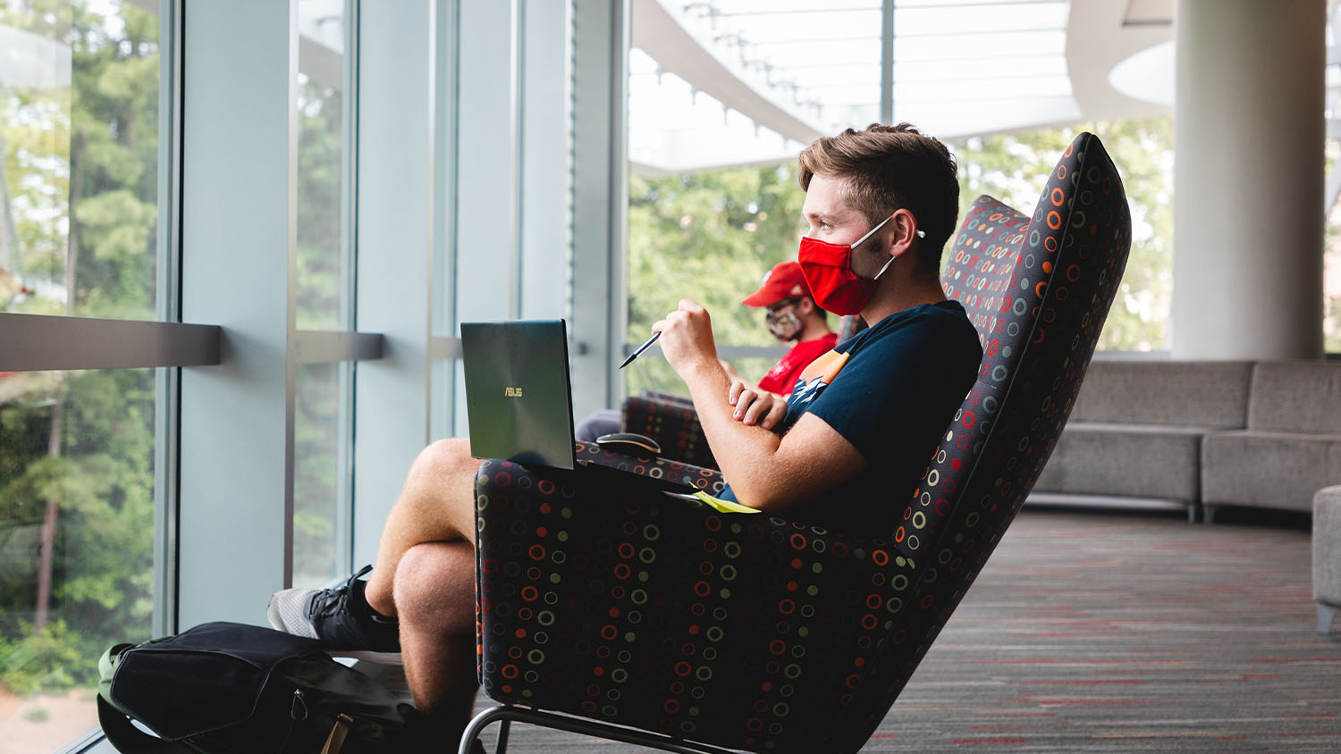 A masked, male student with a laptop in his lap looks out the window in Talley Student Union
