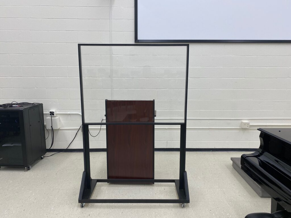 Plexiglass barrier around a podium in a music classroom
