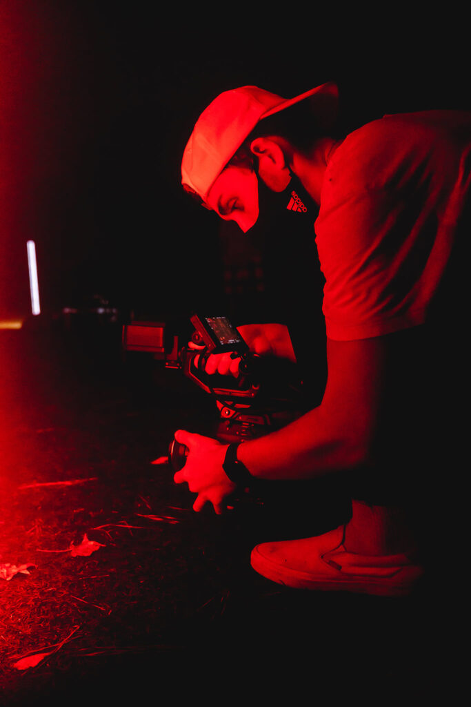 Tolar Ray in red lighting using his camera