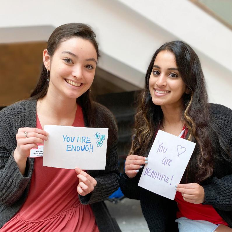 "Two Mental Health Ambassadors hold up signs that read ""You Are Enough"" and ""You Are Beautiful."""