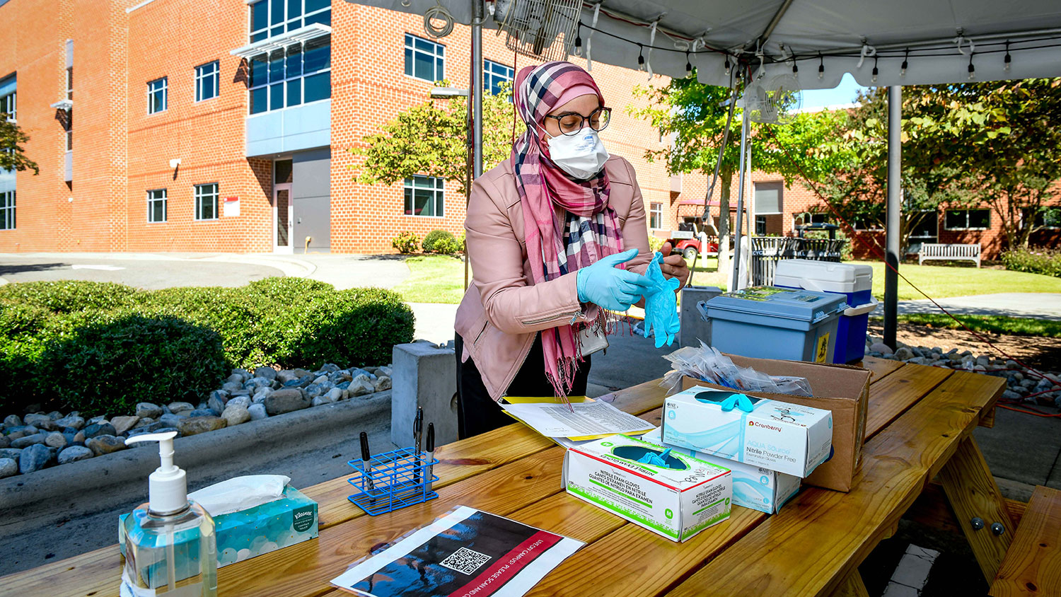 masked and gloved woman working at COVID testing tent on NC State's campus