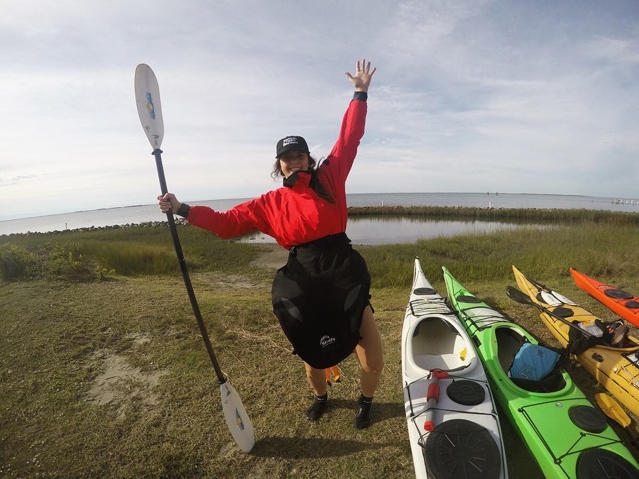 Alyssa Stroker holds up a paddle next to some canoes