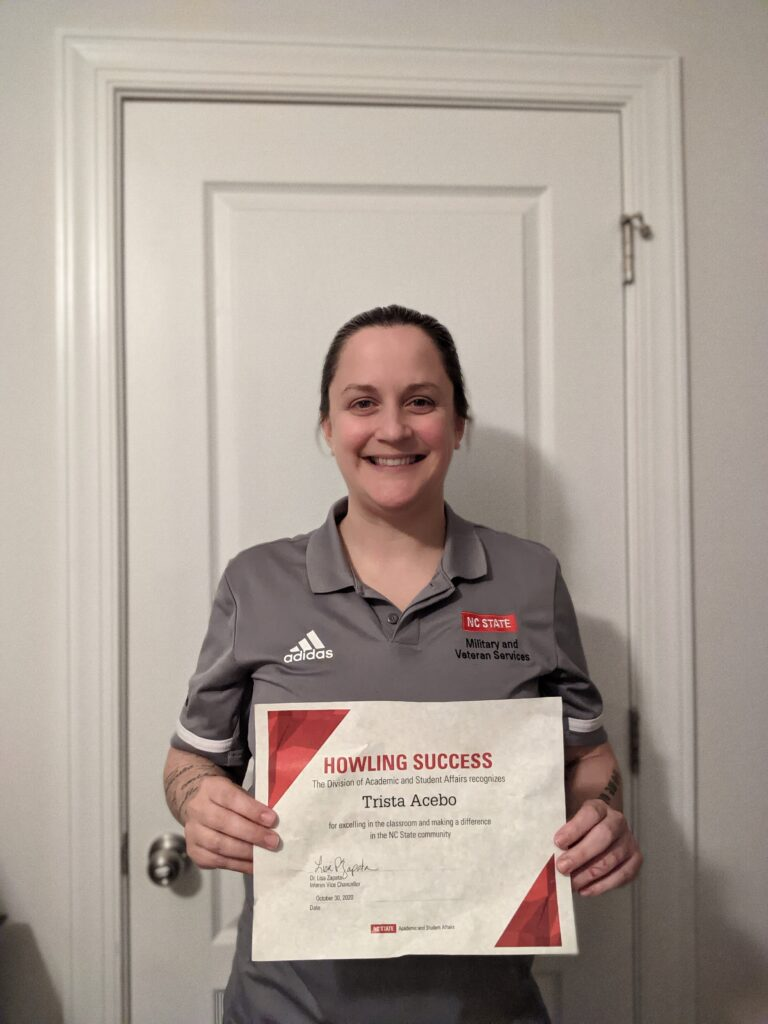 Trista Acebo, holding a certificate in front of a white door