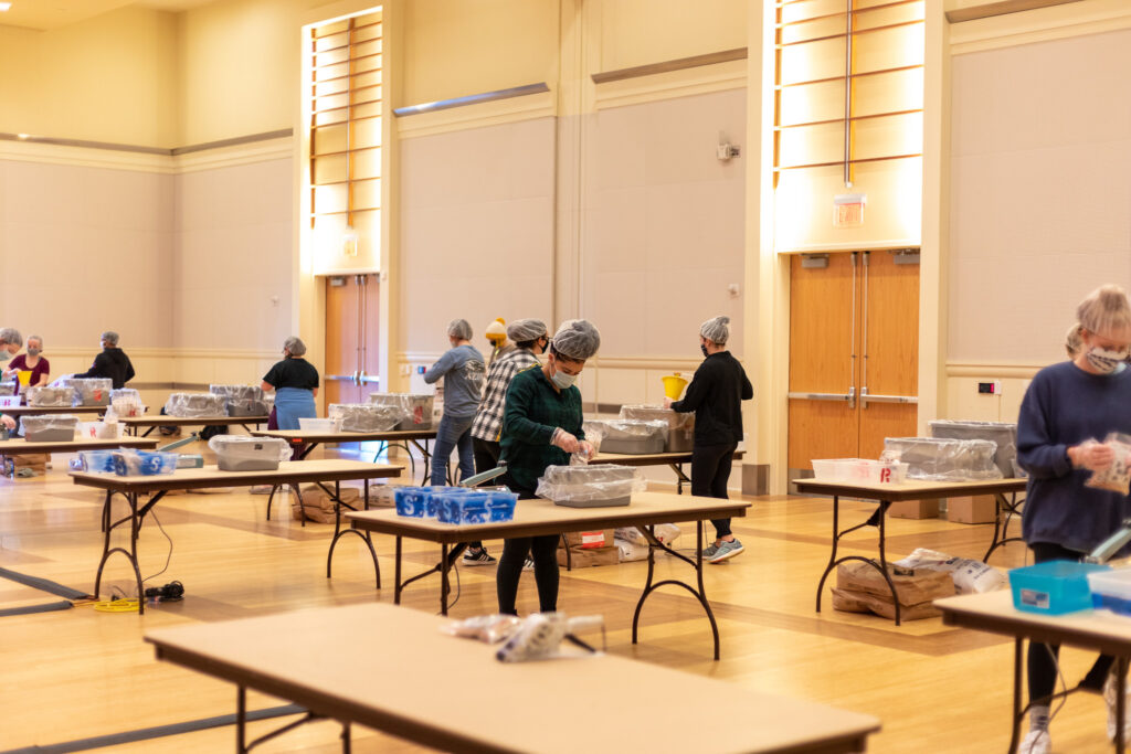 Masked students box meals at individual tables in the Talley Ballroom