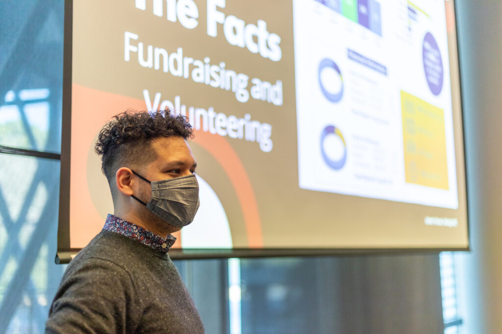 A masked student stands in front of a screen about volunteering