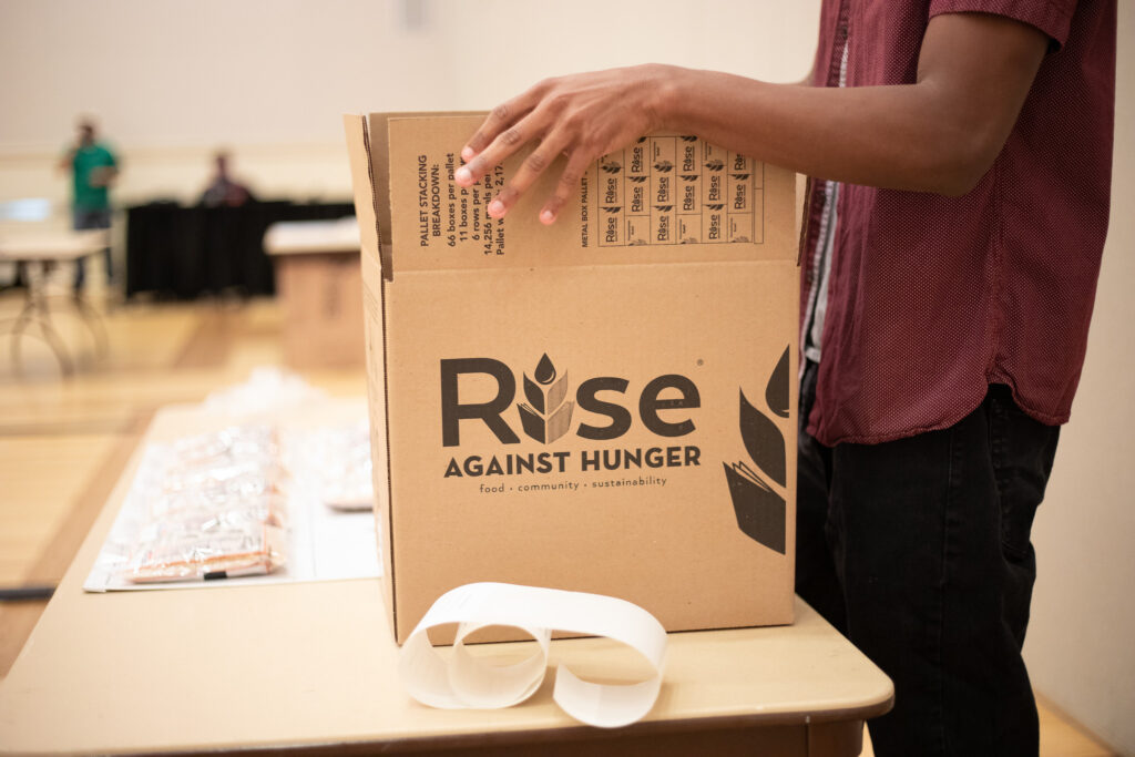 Close up of a box being sealed by student hands