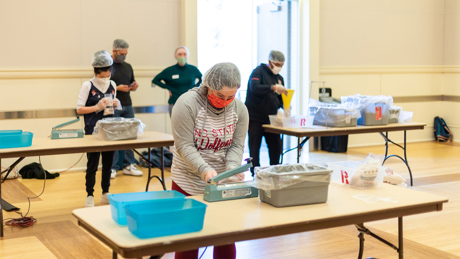 Students stand at tables and pack meals into boxes