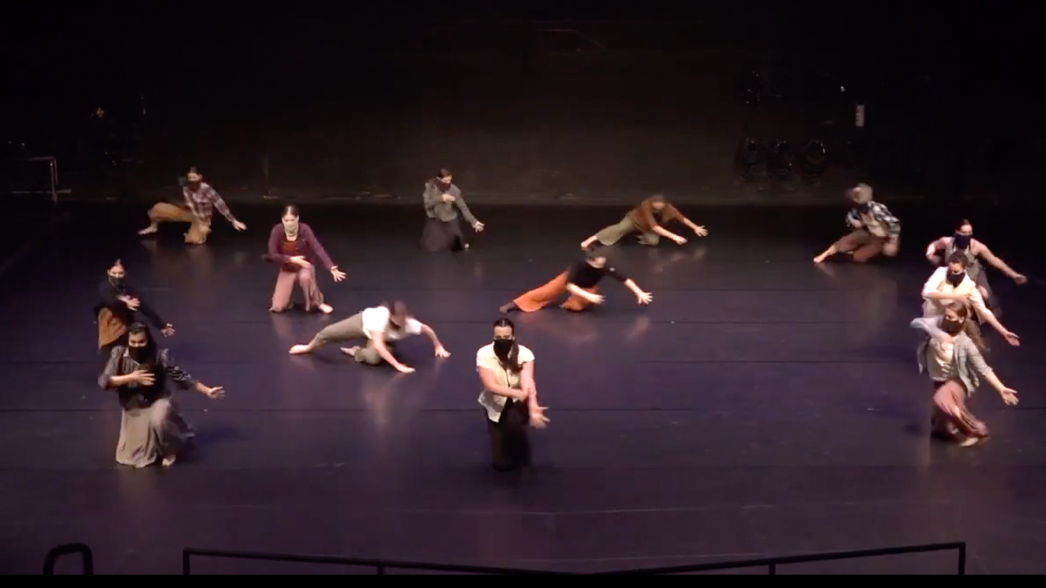 Masked students dance on stage as part of the Against the Railing project last April