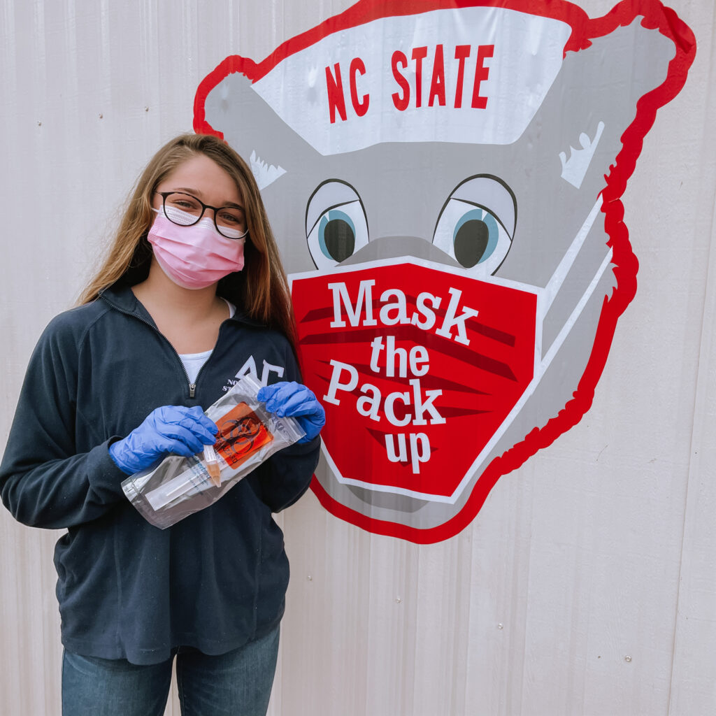 "A masked, female student holds a test kit in front of a sign that reads ""Mask the Pack Up"""