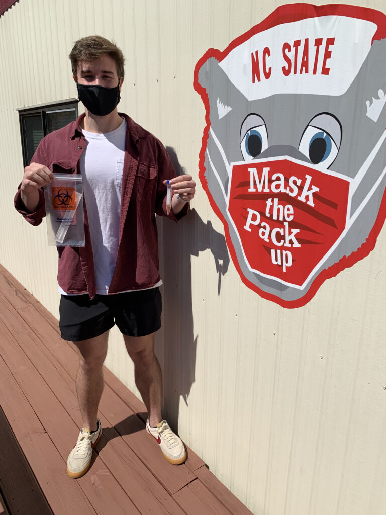 "A male, masked student holds a COVID-19 test kit next to a sign that reads ""Mask the Pack Up."""