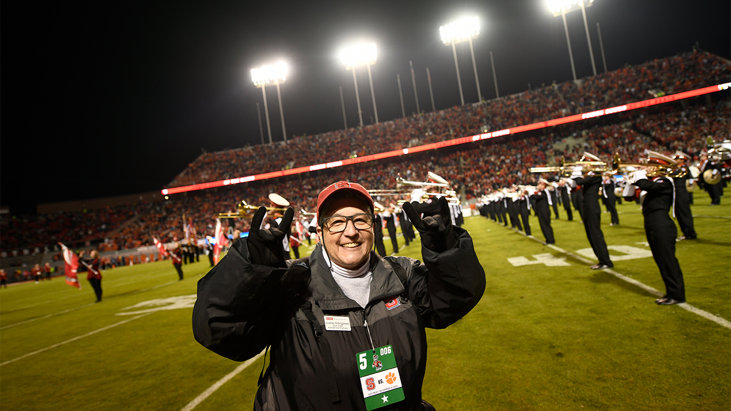 Justine Hollingshead making a wolfie sign on the field at an NC State football game