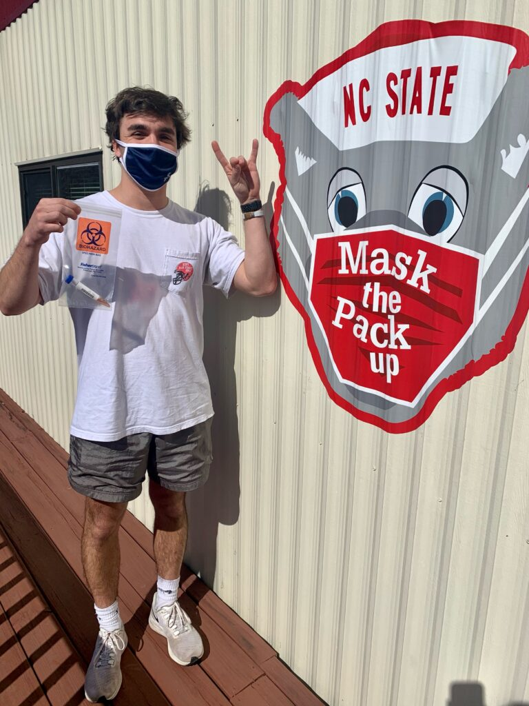 "A masked, male student makes a wolfie sign in front of a sign that reads ""Mask the Pack Up"""