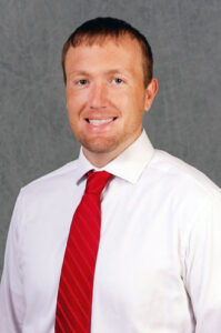 Ben Strunk in a white shirt and red tie