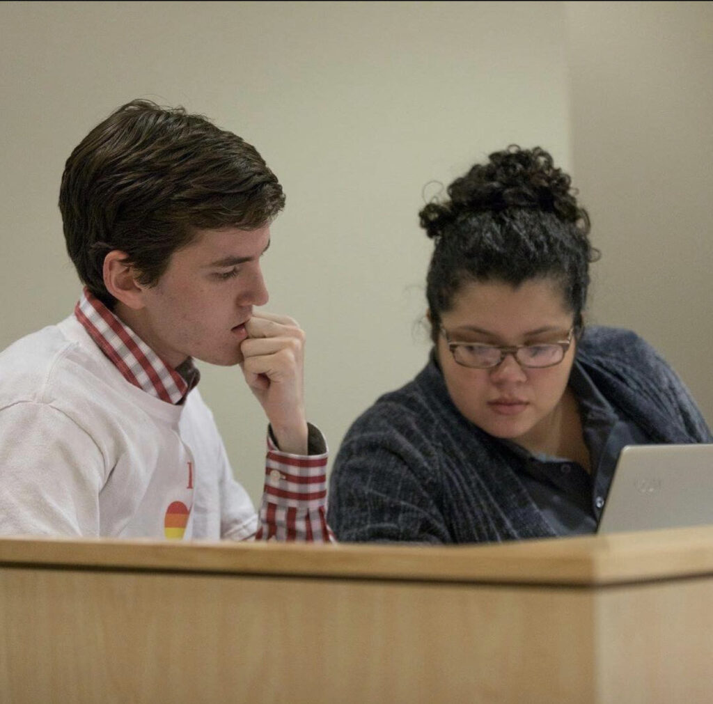 Moravec and Gonzalez working together at a desk in the Student Senate chamber