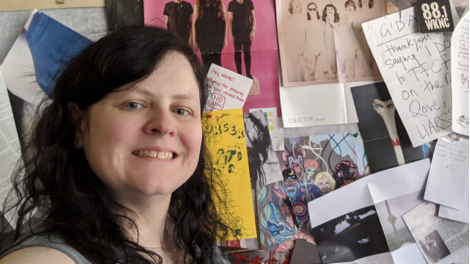 Jamie Lynn Gilbert in front of a wall full of music-related posters