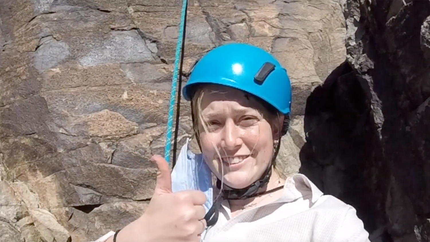 Massey Stichter wearing a teal helmet and making a thumbs up sign while rock climbing