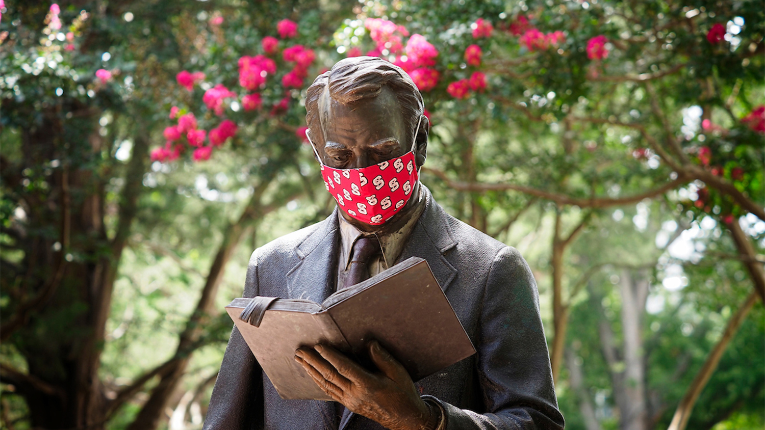 Statue of a professor in a red mask reading a book