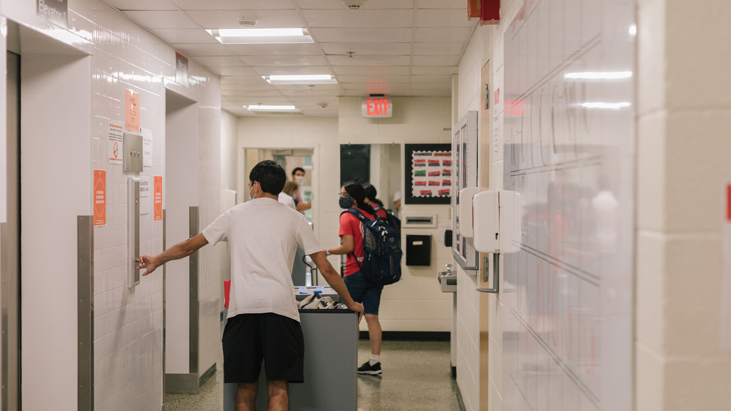 A student pushes their moving cart along a hallway in a residence hall