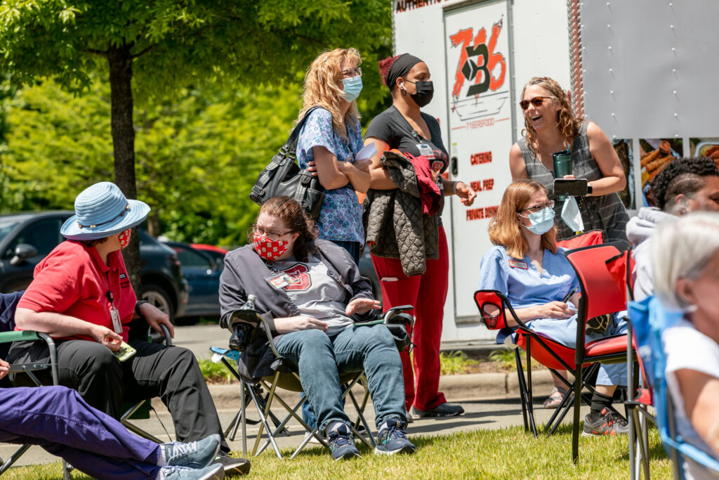 Student Health employees listen to music and talk on the lawn