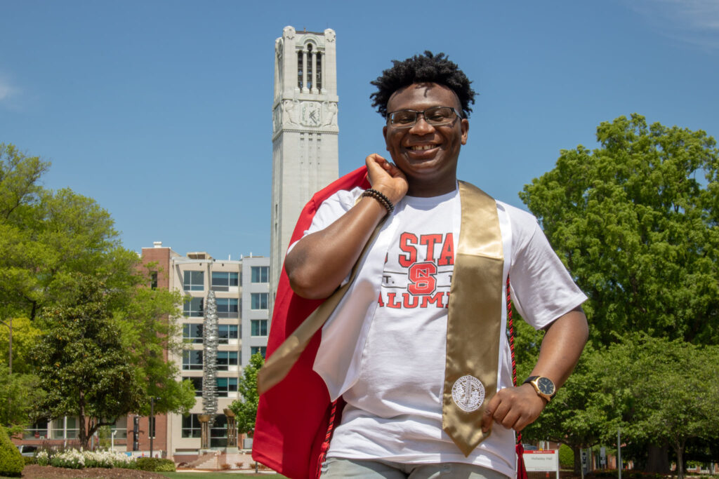 Tirrezz Hudson with a red graduation robe slung over his shoulder, bell tower in the background