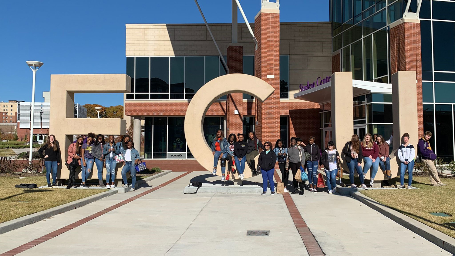 A large group of students in front of large concrete ECU letters on ECU campus