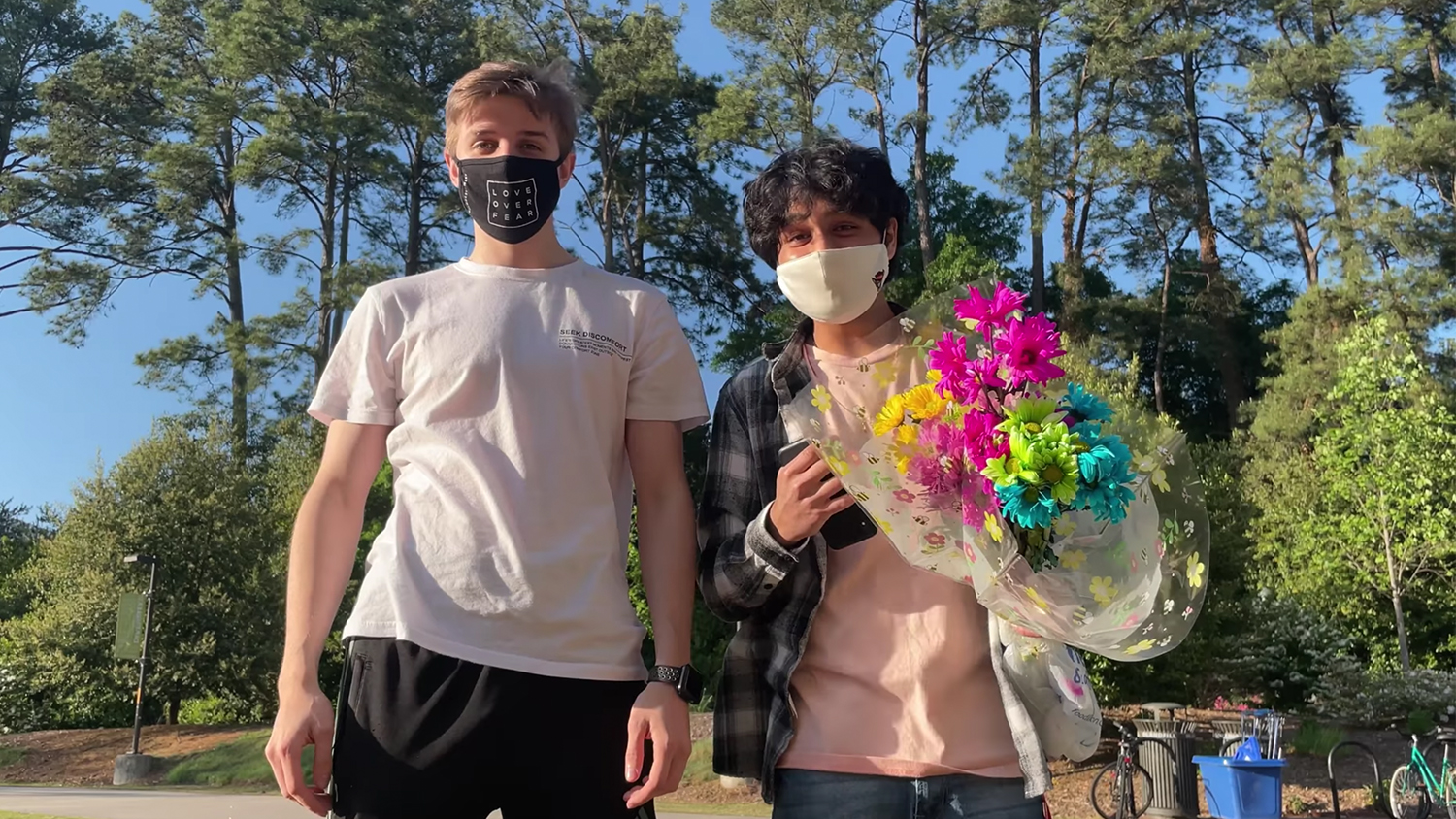 Sean Deardorff and Tejas Kakade wearing masks, holding flowers in an outdoor setting