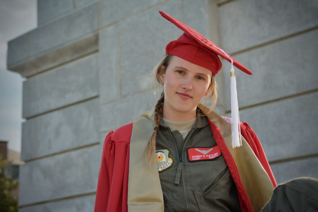 Hannah Fletcher in red graduation robes and red cap, with Air Force flight suit underneath, standing at the base of the bell tower