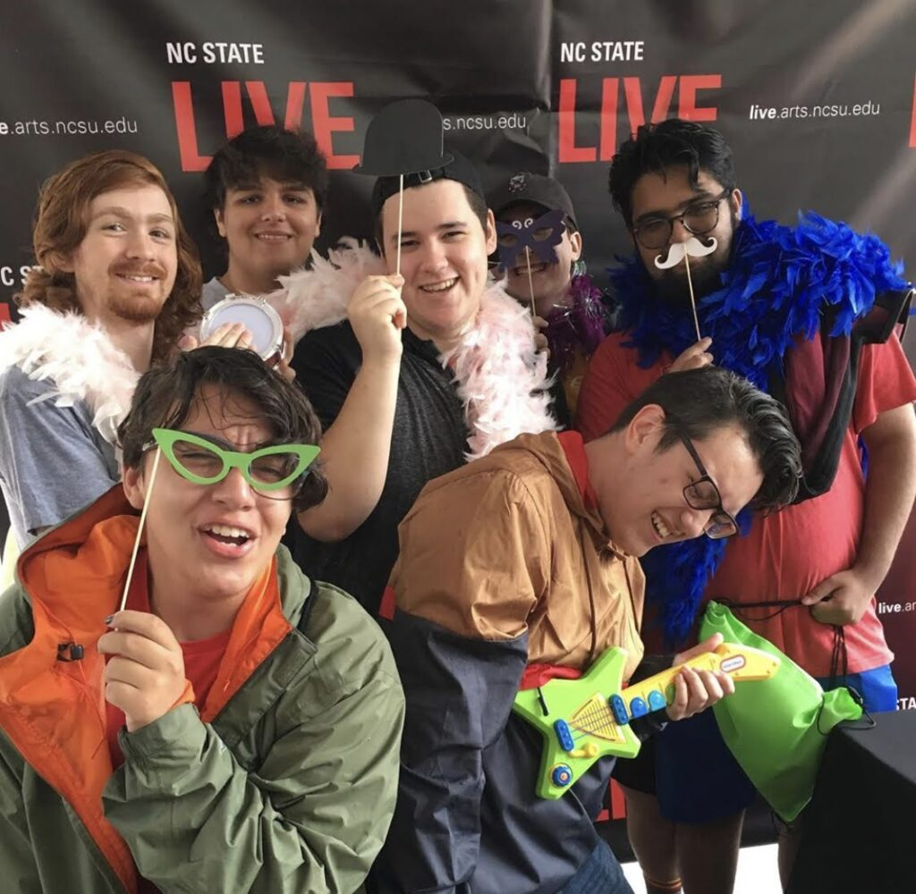 Ryan Unger and a group of friends pose in funny positions in front of a poster with NCState LIVE written on it.