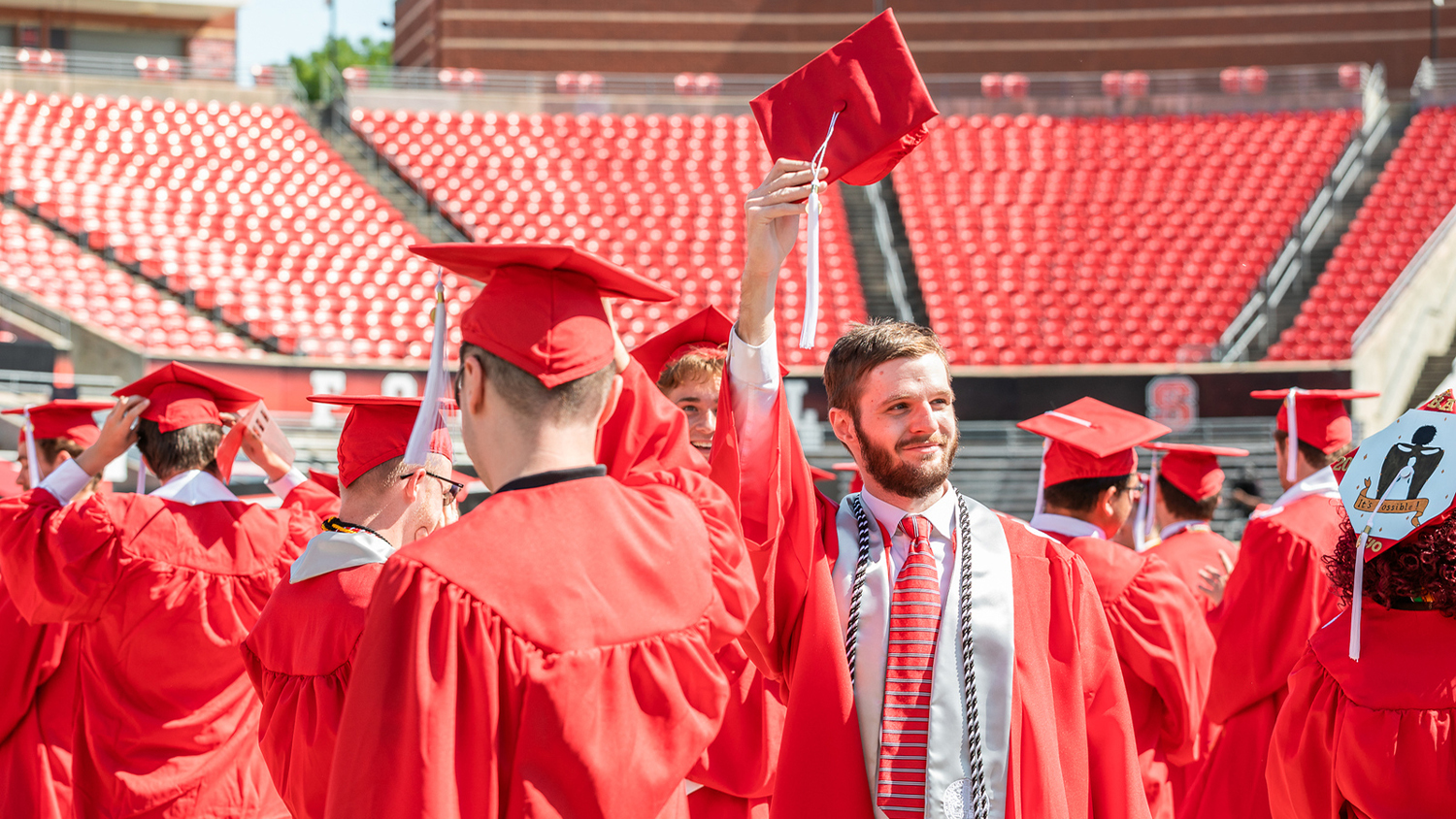 Among several graduates in red robes and hats, one male graduate holds his hat up in the air and smiles