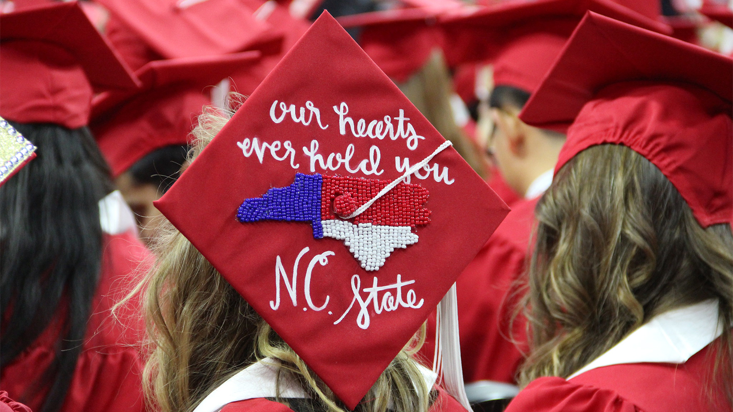 """The top of a graduate's hat that reads """"Our hearts ever hold you, NC State"""""""