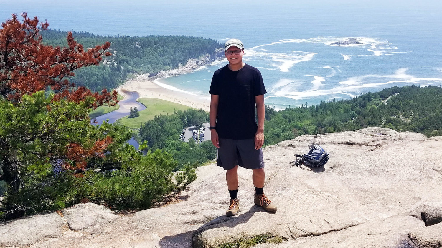 Nikhil Milind standing on a mountain overlooking the ocean