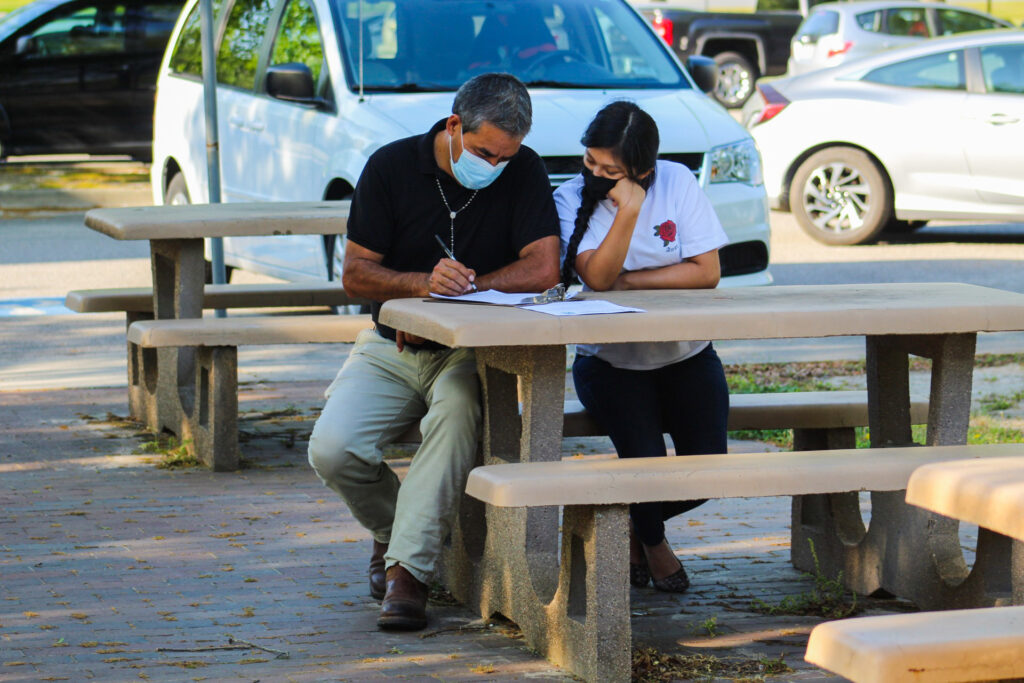 A student and parent, seated at a picnic table, fill out college forms together