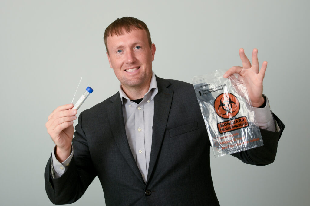 Ben Strunk in a suit, holding a COVID-19 test kit