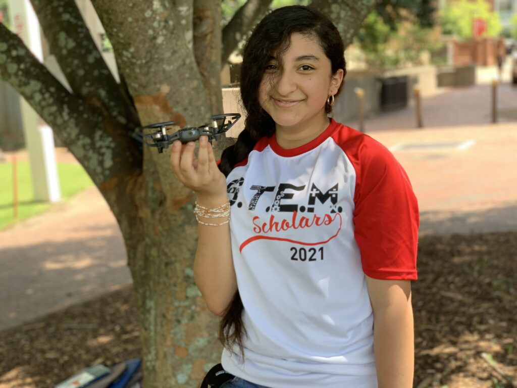 """A student in a shirt that reads """"STEM Scholars 2021"""" smiles and holds up their drone"""
