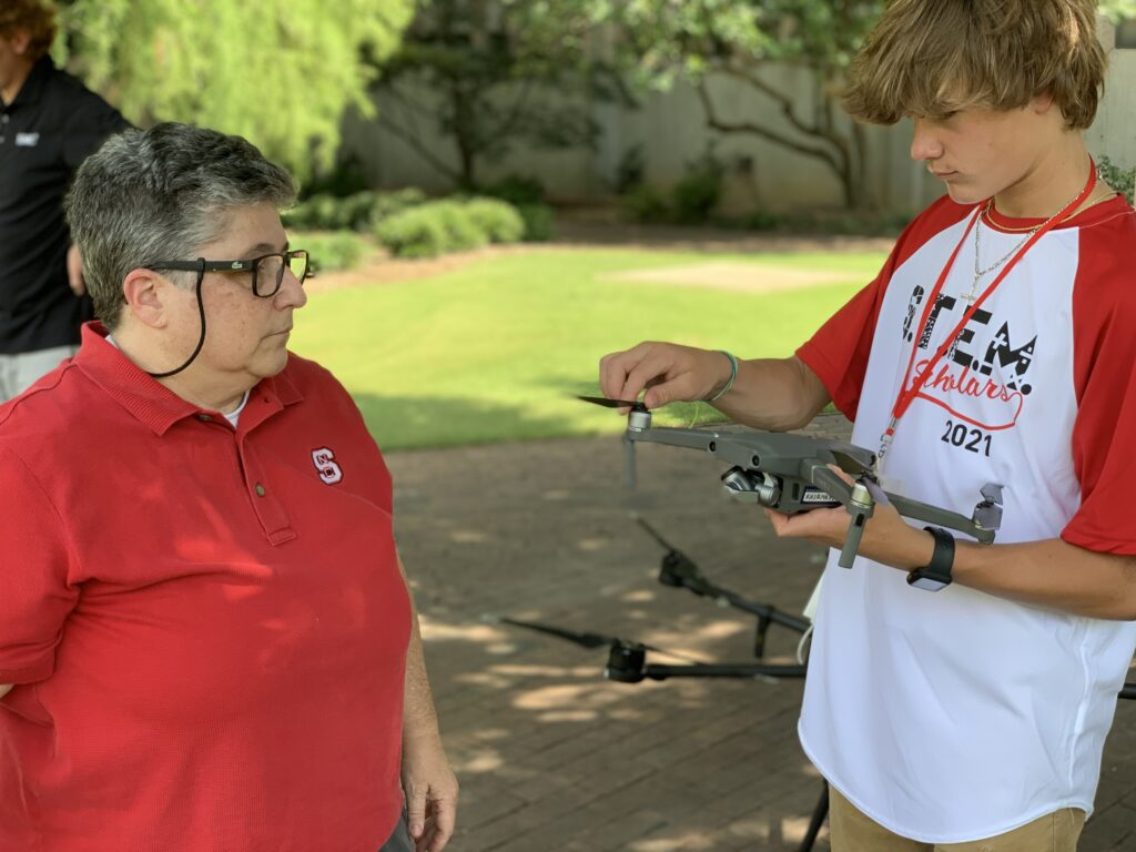 Justine Hollingshead helps a student configure their drone outside on the Court of Carolina