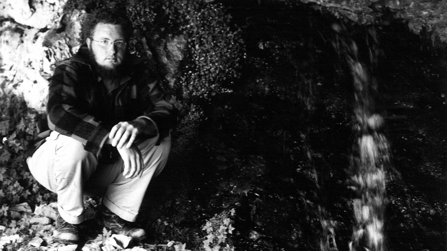 A black and white photo of Roger Manley in Mavroneri, the Cave of the Styx