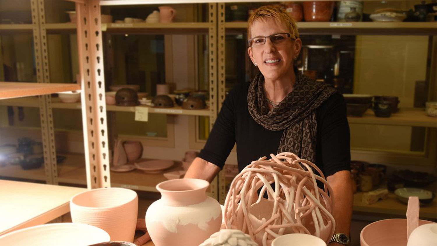 Carol Fountain Nix sitting at a desk with pottery displayed in front of her