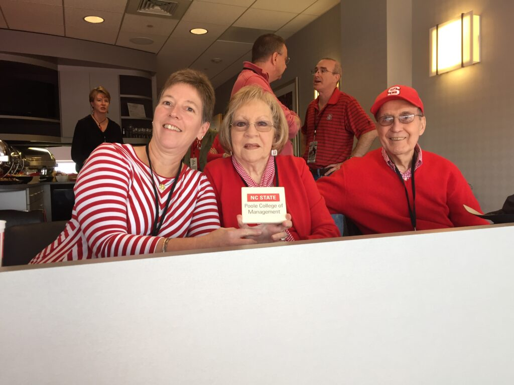 Lori Constantino with her parents, holding up a sign for NCState's Poole College of Management