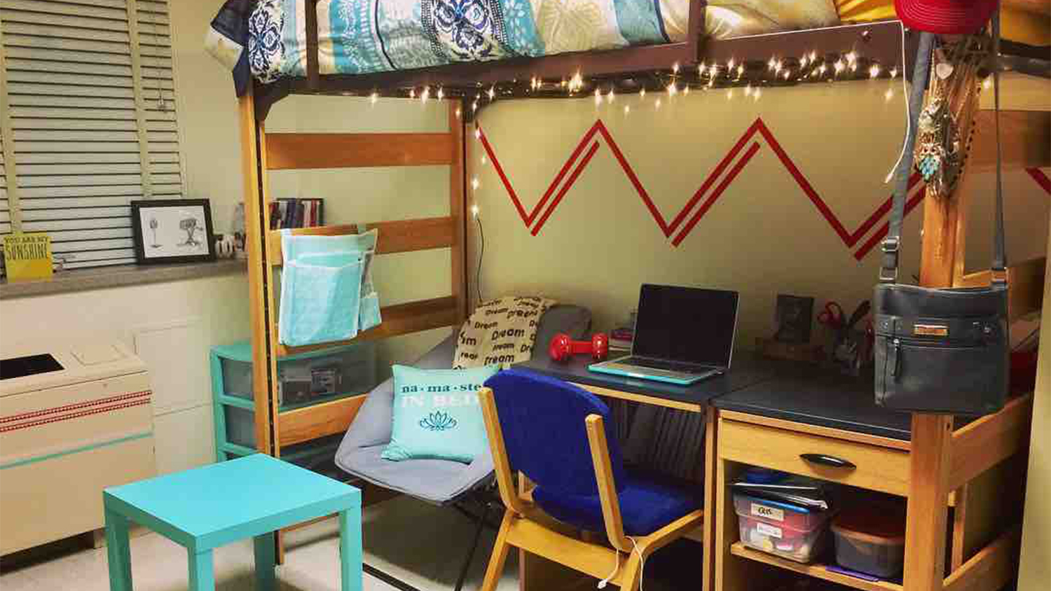 A residence hall room with lofted bed with a desk and fold out chair underneath